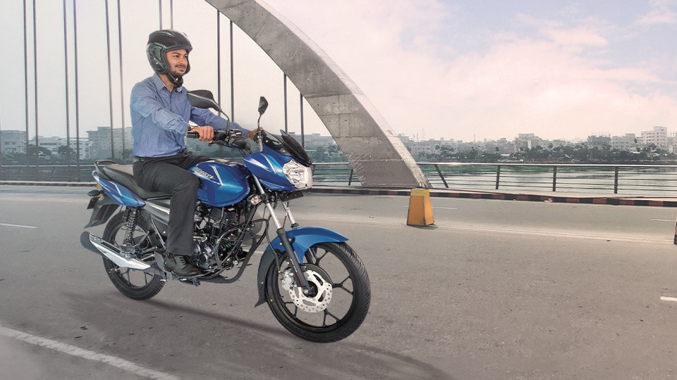 A man riding black and blue color Bajaj discover 110cc  Disk motorcycle on the road with blue helmet