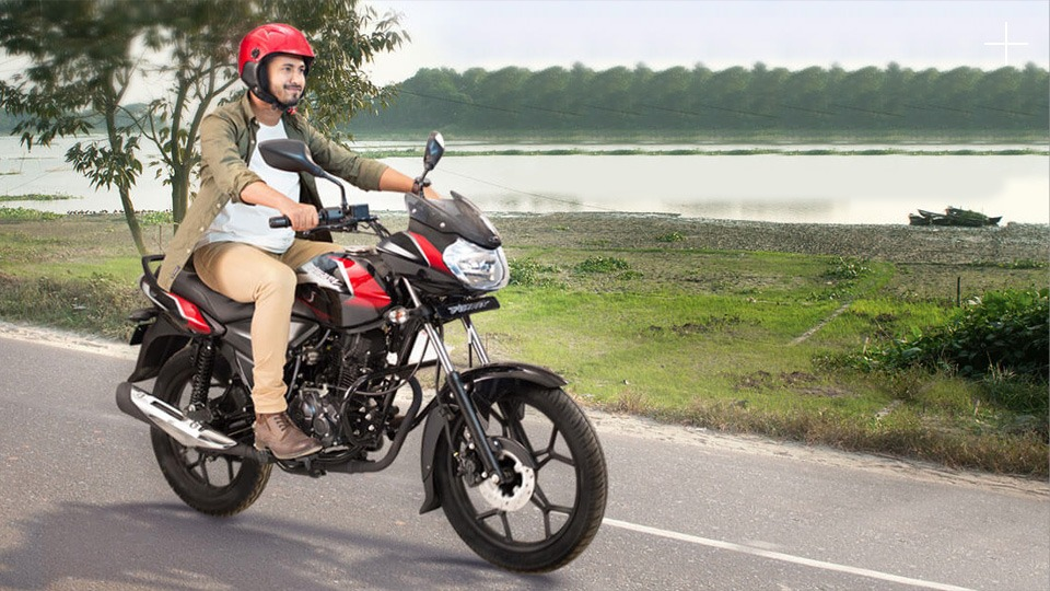 man riding black and red color bajaj discover 125cc disc motorcycle on the road with red helmet