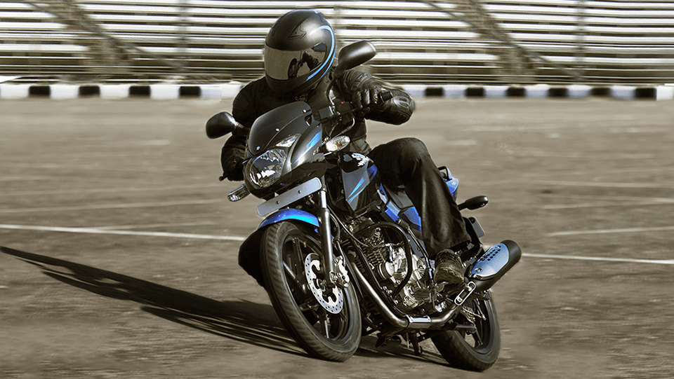 A biker is riding black and blue color Bajaj Pulsar 150 Twin Disk Motorcycle wearing black leather jacket and helmet
