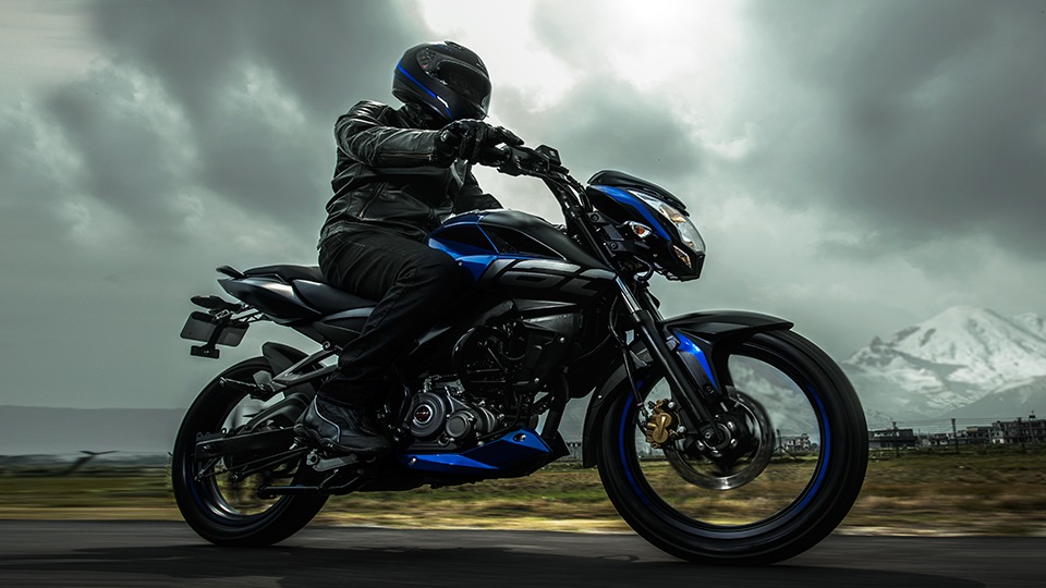 A Biker is Riding Black and Blue Color Bajaj Pulsar NS 160 Twin Disk Motorcycle Wearing Black Leather Jacket and Helmet
