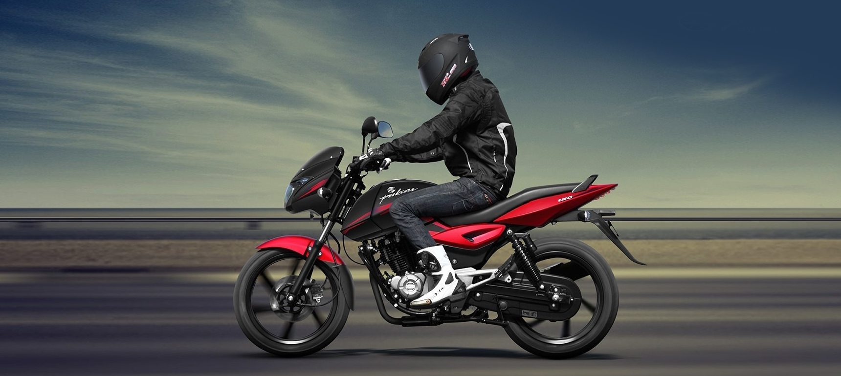 A biker is riding on a open road with black and red color Bajaj Pulsar 150 Twin Disk Motorcycle wearing black leather jacket and helmet