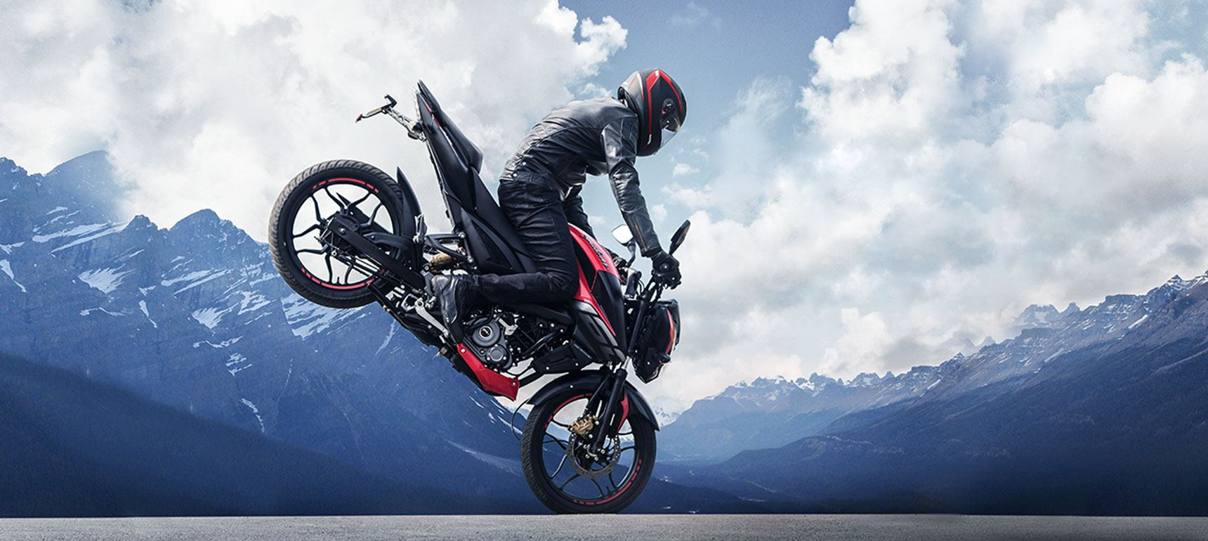 A biker is making stunt with black and red color bajaj Pulsar NS 160 Twin Disk Motorcycle wearing black leather jacket and helmet