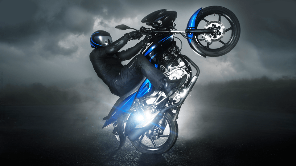 A biker is making stunt with black and blue color Bajaj 150cc Motorcycle wearing black leather jacket and helmet