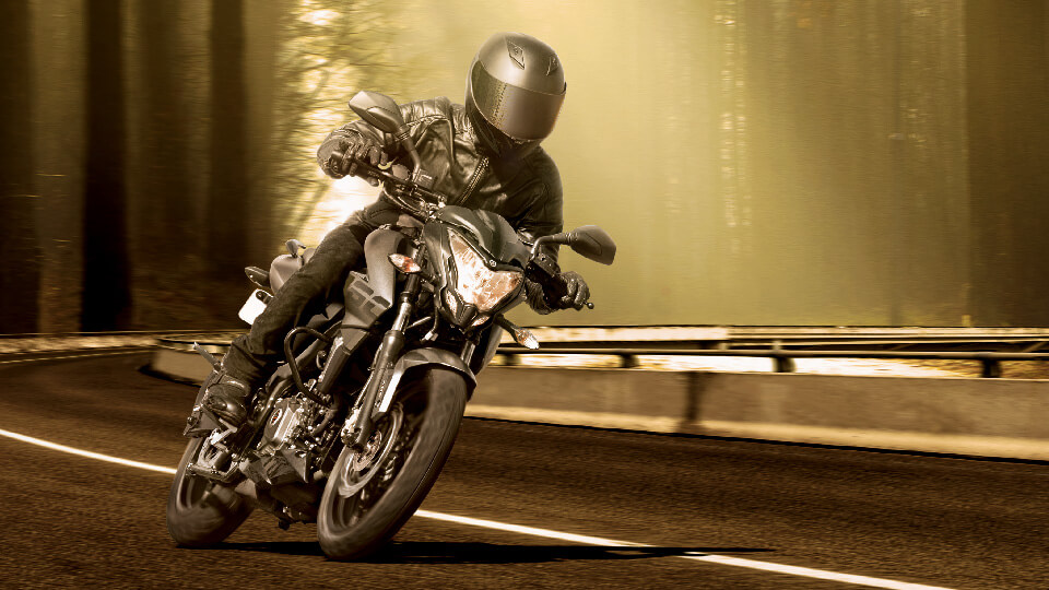 A Biker is Riding Black Bajaj Pulsar NS 160 FI ABS Motorcycle wearing black leather jacket and helmet