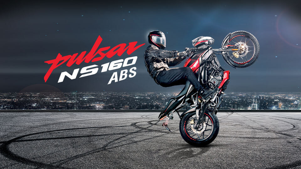 A biker is making stunt with black and red color Bajaj Pulsar NS 160 Twin Disk ABS Motorcycle wearing black leather jacket and helmet