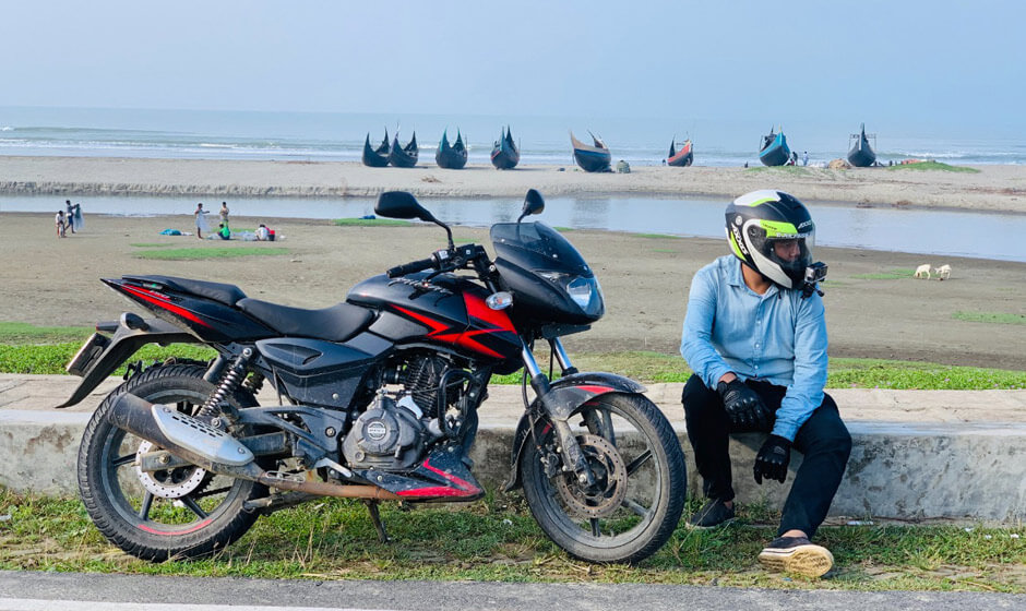 Red Pulsar 150 Twin Disc with Rider beside the Sea