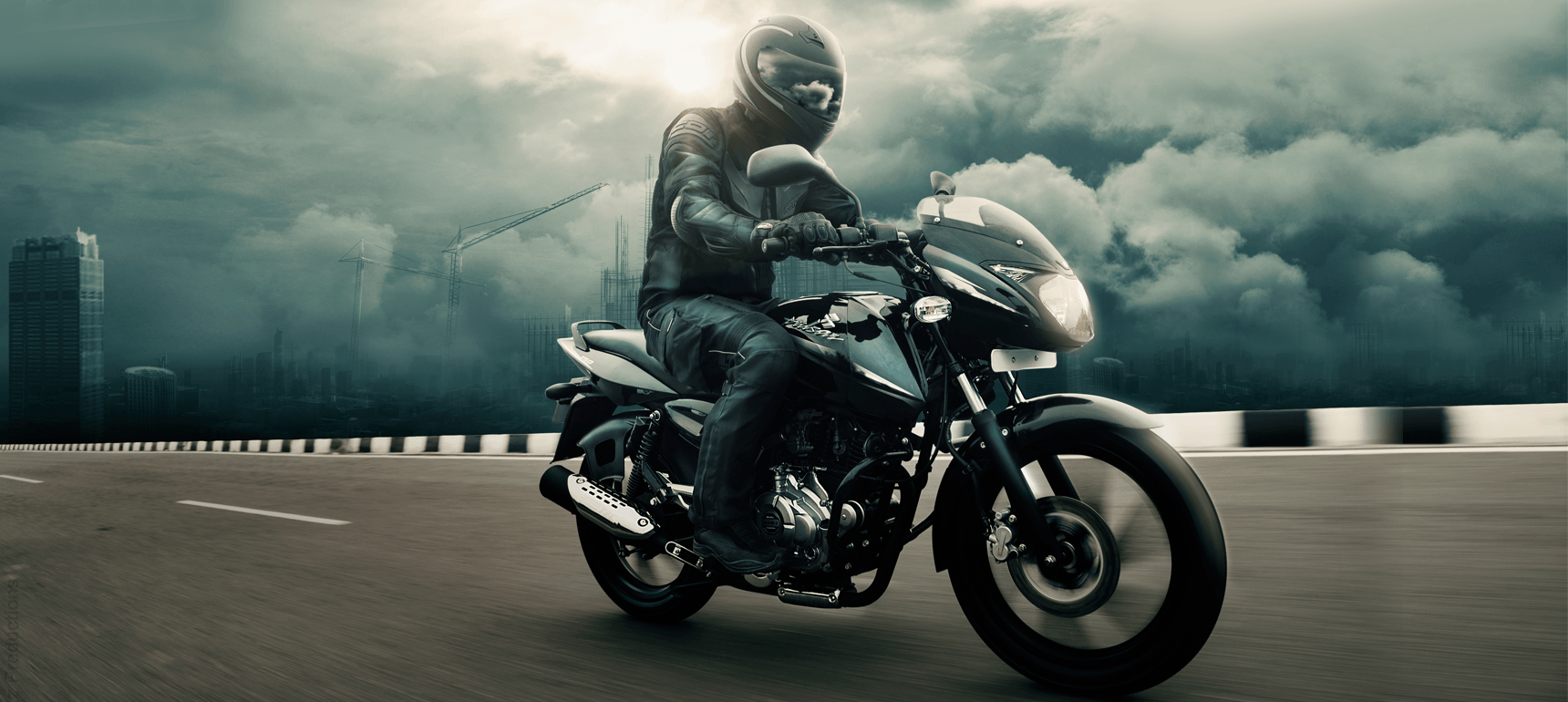 A biker is riding black and blue color Bajaj Pulsar 150cc motorcycle wearing black leather jacket and helmet in open road
